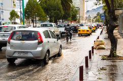 基多,厄瓜多尔- 2016年9月20日:一motocycle和汽车乘驾在一条被充斥的路在基多市在大雨以后 免版税库存照片