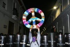 基多,厄瓜多尔- 2015年8月27日:供以人员举行在排队的防暴警察基多市前面的佩带的面部油漆大和平标志 免版税图库摄影