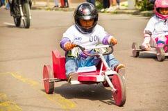 基多,厄瓜多尔- 2017年5月06日:关闭赛跑在市街道的一个未认出的男孩一辆木红色汽车基多 免版税图库摄影