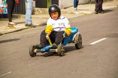基多,厄瓜多尔- 2017年5月06日:关闭赛跑在市街道的一个未认出的男孩一辆木蓝色汽车基多 库存图片