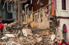 基多,厄瓜多尔- 2016年12月09日:在一栋完全地被破坏的砖瓦房的未认出的firemans在基多市 免版税库存图片