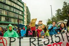 基多,厄瓜多尔- 2015年8月27日:小组恼怒的混杂的青年人阻止横幅和愤怒抗议在城市 库存照片