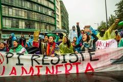 基多,厄瓜多尔- 2015年8月27日:小组恼怒的混杂的青年人阻止横幅和愤怒抗议在城市 库存图片