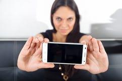 基多,厄瓜多尔- 2017年5月09日:拿着一个现代手机的美丽的妇女使用指向从她在苹果计算机 库存照片