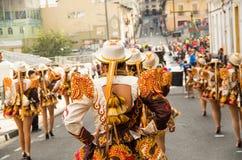 基多,厄瓜多尔- 2016年12月09日:有五颜六色的服装的人们在街道跳舞在一次游行期间在基多 免版税图库摄影