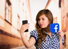 基多,厄瓜多尔- 2016年3月11日:有现代手机的妇女在拿着贴纸facebook象的手上 最大和 库存照片
