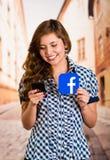 基多,厄瓜多尔- 2016年3月11日:有现代手机的微笑的少妇在拿着贴纸facebook象的手上 库存图片