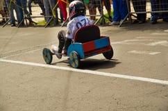 基多,厄瓜多尔- 2017年5月06日:赛跑在市街道的一个未认出的男孩一辆木汽车基多,后面看法 免版税库存照片