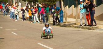 基多,厄瓜多尔- 2017年5月06日:赛跑在市街道的一个未认出的男孩一辆木汽车基多 库存照片