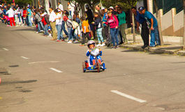 基多,厄瓜多尔- 2017年5月06日:赛跑在市街道的一个未认出的男孩一辆木汽车基多 免版税库存图片