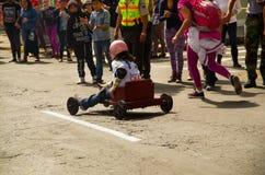 基多,厄瓜多尔- 2017年5月06日:赛跑在市街道的一个未认出的男孩一辆木汽车基多 免版税库存照片
