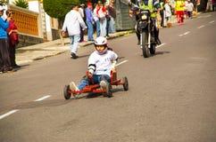 基多,厄瓜多尔- 2017年5月06日:赛跑在市街道的一个未认出的男孩一辆木红色汽车基多 免版税库存图片