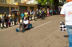 基多,厄瓜多尔- 2017年5月06日:赛跑在都市路的一个未认出的人一辆木汽车在城市里面街道  库存照片