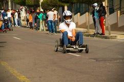 基多,厄瓜多尔- 2017年5月06日:赛跑在都市路的一个未认出的人一辆木汽车在城市里面街道  免版税库存照片