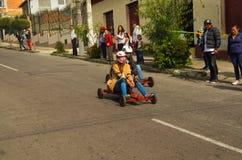 基多,厄瓜多尔- 2017年5月06日:赛跑在都市路的一辆木汽车的一对未认出的夫妇在城市里面街道  免版税库存图片