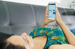 基多,厄瓜多尔- 2017年5月09日:说谎在有现代手机的在手上,登录画面电子港湾长沙发的美丽的妇女 免版税库存照片