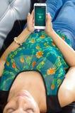 基多,厄瓜多尔- 2017年5月09日:说谎在有现代手机的在手上,登录画面长沙发的美丽的妇女 免版税库存照片