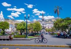基多,厄瓜多尔- MARZO 23日2015年:未认出的通过独立在基多摆正的trought,天的人和他的bycicle 免版税库存图片