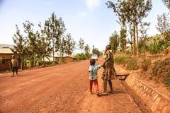 基布耶,卢旺达,非洲- 2015年9月11日:未知的孩子 汽车在土路去并且培养尘土云彩  库存照片