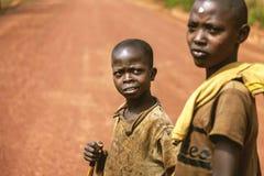 基布耶,卢旺达,非洲- 2015年9月11日:未知的孩子 红色土地的两个小非洲男孩 免版税库存图片