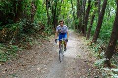 基希纳乌,摩尔多瓦- 2017年7月16共和国日:队的卡秋沙骑自行车者骑沿森林公路的一辆自行车 免版税库存图片
