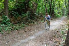 基希纳乌,摩尔多瓦- 2017年7月16共和国日:队的卡秋沙骑自行车者骑沿森林公路的一辆自行车 库存照片