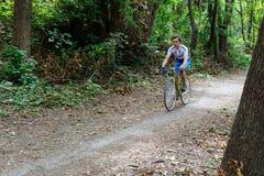 基希纳乌,摩尔多瓦- 2017年7月16共和国日:队的卡秋沙骑自行车者骑沿森林公路的一辆自行车 库存图片