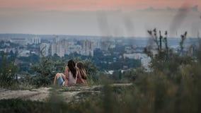 基希纳乌,摩尔多瓦- 2016年7月17日, :站立在小山的两个女孩观看日落在基希纳乌 免版税库存图片