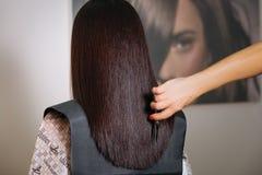 基希纳乌,摩尔多瓦-莒勒石19共和国日2017年:妇女从后面的` s发型 手理发师剪刀 浴巾路易威登 图库摄影