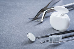 基本的牙齿工具、绣花丝绒和刷子灰色表面上 库存图片