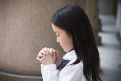 基本祈祷的女小学生 库存图片