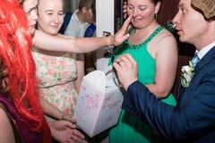 基洛夫,俄罗斯- 2018年7月27日:在新娘的赎金的乐趣的期间新郎 一部分的传统俄国婚礼 免版税库存图片