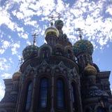 基督喋血大教堂在明亮的天空蔚蓝背景的圣彼德堡与云彩的 底视图 图库摄影
