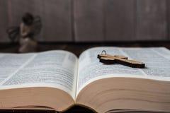 基督徒发怒圣经和天使在木背景 库存照片