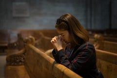 基督徒女孩是坐和祈祷与在的伤心 免版税库存图片