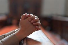 基督徒女孩是坐和祈祷与在的伤心 库存图片