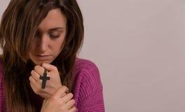 年轻基督徒妇女拿着十字架的和赞美诗预定 库存图片