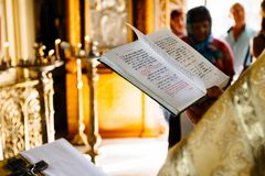 基督徒教士读书教会书,教士读在圣经的一祈祷 免版税库存照片