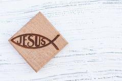 基督徒鱼标志在白色葡萄酒木背景的木头雕刻了 库存照片