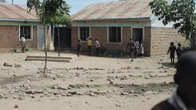 基苏木,肯尼亚- 2018年5月15日:小组踢橄榄球的制服的非洲孩子在校园 恶劣的村庄 股票视频