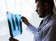 基辅地区,乌克兰- 10月12 2016年:博士 治疗师在看X-射线的办公室耐心` s肺 免版税库存图片