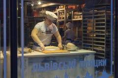 基辅,乌克兰- 2018年2月25日:供以人员厨师煮熟的土豆薄烤饼在商店窗口里 免版税库存照片