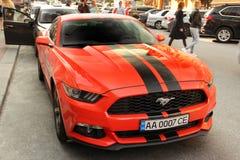 基辅,乌克兰- 2019年5月3日:橙色Ford Mustang在城市 免版税图库摄影