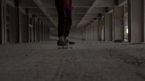 基辅,乌克兰- 2018年8月17日:男孩溜冰板者在沿黑暗的停车场的一个委员会移动 股票录像