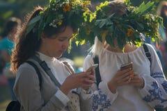 基辅,乌克兰- 2017年7月06日:花圈的女孩从与智能手机的花在一个传统斯拉夫的假日的庆祝 图库摄影