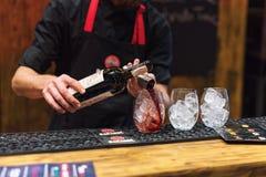 基辅,乌克兰- 2016年10月30日, :男服务员节日 年轻英俊的侍酒者做鸡尾酒 免版税库存照片