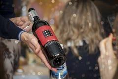 基辅,乌克兰- 2016年3月26日:在好藤商店的品酒 斟酒服务员倒干红葡萄酒入玻璃 库存照片