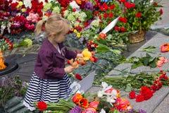 基辅,乌克兰- 2015年5月9日:女孩拿着一个玩具在纪念碑下落的战士 库存图片