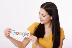 基辅,乌克兰- 2016年8月22日:妇女在灰色背景的纸递拿着谷歌略写法打印 谷歌是美国 免版税库存图片