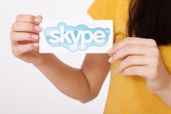 基辅,乌克兰- 2016年8月22日:妇女在灰色背景的纸递拿着Skype略写法打印 Skype是a 库存图片